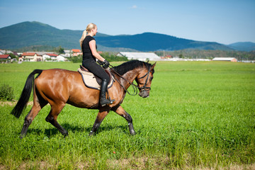 Beautiful young blonde woman riding a horse