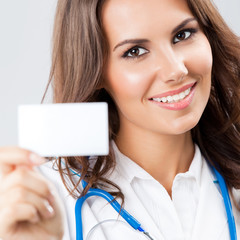 Young female doctor showing blank business card