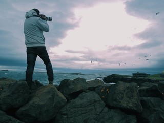 Photographer over rocks shooting seagulls by the sea