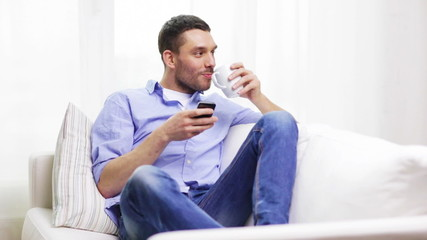 smiling man with smartphone and a cup at home