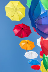 Colourful umbrellas against a blue sky