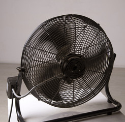 Electric fan with blades turning to produce cool air