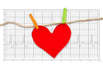 Red paper heart hanging on the clothesline on  electrocardiogram