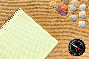 Yellow checkered notepad and compass in sand