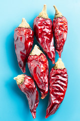 Dried chili peppers on a light blue background