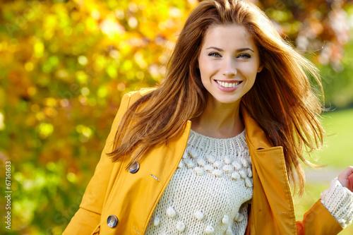 Leinwandbild Motiv Beautiful elegant woman standing in a park in autumn