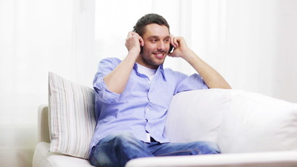 smiling young man with headphones at home