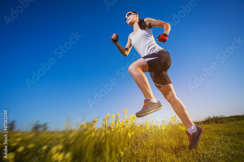 canvas print picture Young woman jogging in nature