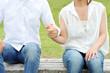 屋外のベンチに座って手をつなぐカップル