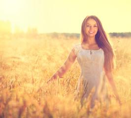 Beautiful teenage model girl in white dress running on the field