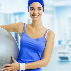 Young happy woman with fitness ball, at gym