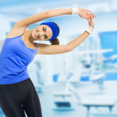 Young happy woman doing fitness exercises, at gym