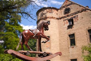 Antikes Schaukelpferd vor historischem Schloss