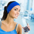 Woman in sportswear drinking water, at gym