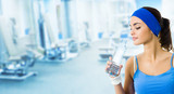 Woman in sportswear drinking water, at gym