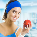 Fototapety Woman in sportswear with apple, at gym