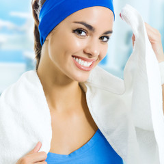 Smiling young woman in fitness wear with towel, at gym