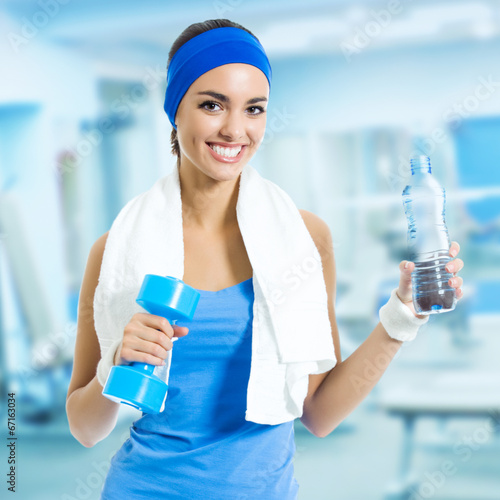 Woman in fitness wear with water, at gym