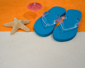 Beach slippers, towel on sand background