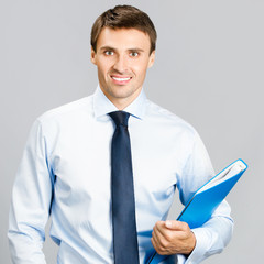 Business man with folder, on gray