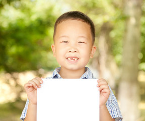 Asian boy  6 years old with a sheet of paper in the park