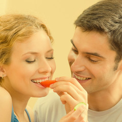 Cheerful young couple eating together tomatoes