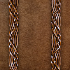Background of brown leather with braided leather straps