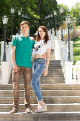 Trendy young couple posing on a flight of stairs