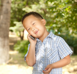 funny asian boy with a mobile phone in a park