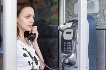 Woman holding the receiver in a telephone booth