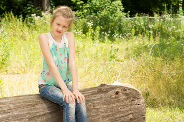Little girl sitting in woodland on a log