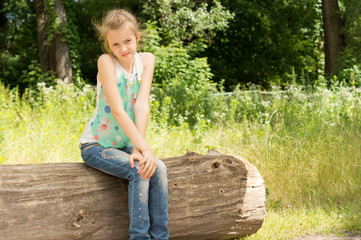 Cute coy little girl sitting on a log in woodland
