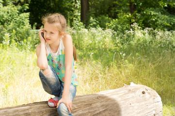 Cute observant little girl on a log