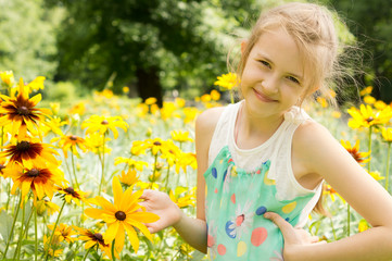 Smiling young girl playing in yellow flowers