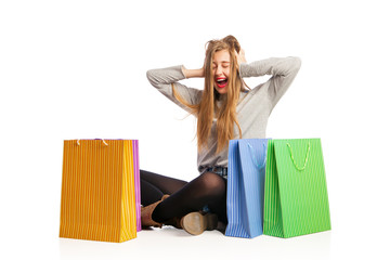 Excited woman sitting among colorful shopping bags