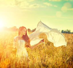 Beauty girl in white dress on summer field enjoying nature