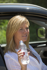 Woman driver drinking water from a plastic bottle