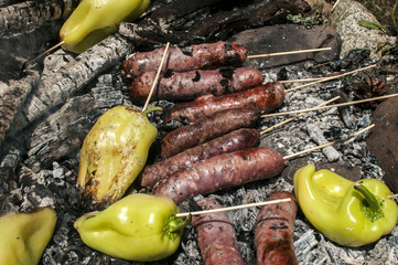 Raw sausages and peppers preparing on hot fireplace wood embers