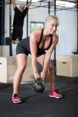 Woman trains with kettlebell in fitness gym