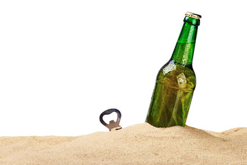 Beer bottle in the sand isolated