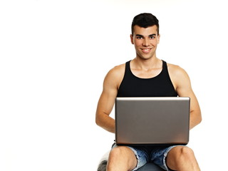 Young man sitting on the sport ball with computer