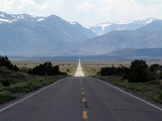 long straight road to faraway mountains in Nevada, USA