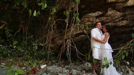 Young couple on a beach near a cliff