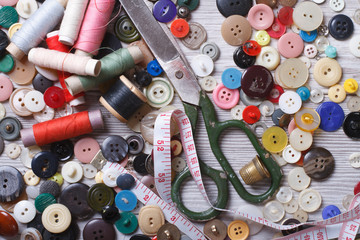 Old buttons, scissors, thimble, thread on a wooden background
