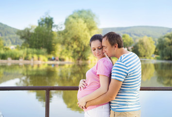 Pregnant couple by the lake