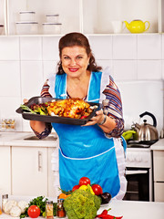 Mature woman preparing chicken at kitchen.