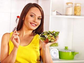 Woman eating salad at kitchen.