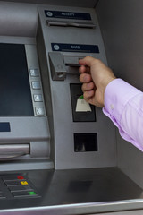Male hand inserting card into cash machine