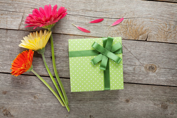 Three colorful gerbera flowers with gift box