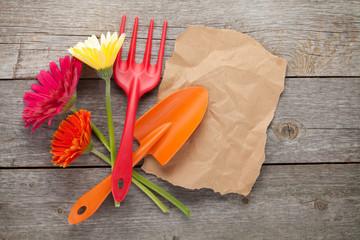 Gardening tools and gerbera flowers